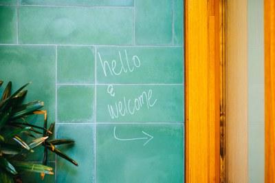 """Worte """"hello and welcome"""" auf einer türkisfarbenen Kachelwand geschrieben"""